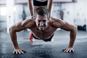 Man doing push-ups with woman kneeling on his back